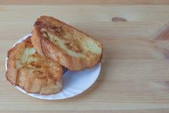 Stekte rostade bröd av vitt bröd som in blöts, mjölkar och ägget på träbakgrund Royaltyfri Fotografi