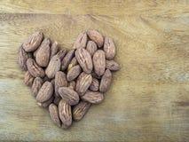 Stekte salta mandlar som bryner hud som läggas ut i formen av en hjärta på den grova träyttersidan Royaltyfria Foton