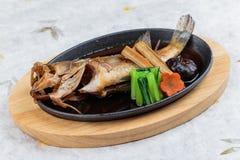 Stekte snapper med rädisan, moroten, shiitaken och choy summa i varm platta på träplattan på japanskt papper för washi Fotografering för Bildbyråer