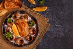 Stekte sniglar med citronen, bagetten och persilja Royaltyfri Fotografi