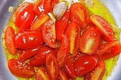 Stekte tomater, vitlök och lökar i pannan Royaltyfri Bild