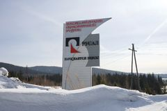 Stele with the logo of the company `RUSAL` stands on the road against the background of the taiga. BELOGORSK, RF - March 18, 2018: Stele with the logo of the stock image