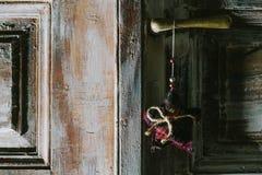 Stella decorativa di natale che appende sulla vecchia maniglia di porta Immagine Stock