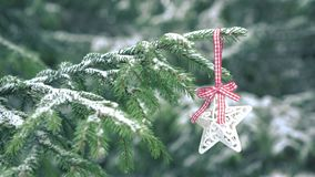 Stella della decorazione di Natale che appende sull'albero di abete nevoso stock footage