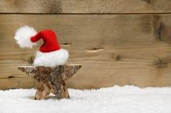 Stella di legno con il cappello di Santa su fondo di legno - idea fatta a mano Immagine Stock Libera da Diritti