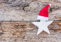 Stella di natale bianco con il cappello rosso di Santa su vecchio fondo di legno con lo spazio della copia fotografia stock
