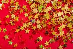 Stella dorata su un fondo rosso immagine stock