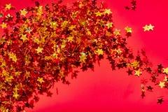 Stella dorata su un fondo rosso immagini stock
