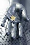 Stella dorata sulla mano futuristica d'argento Immagine Stock Libera da Diritti