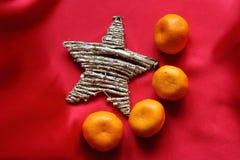 Stella e mandarini sul color scarlatto del panno come un simbolo della bandiera della Cina Immagine Stock