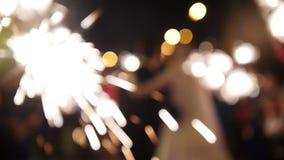 Stella filante in mani sulle nozze - sposa, sposo ed ospiti tenenti le luci dentro, defocused archivi video