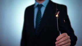 Stella filante nelle mani di un uomo d'affari feste, natale e nuovo anno nell'affare Movimento lento stock footage