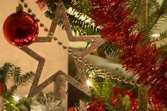 Stella, luci, bagattella e ghirlande nell'albero di Natale immagine stock