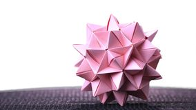 Stellated origami ball on white background. Spiky origami decoration isolated on white background. Modular cardboard product stock footage