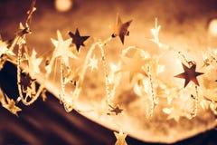 Stelle brillanti dorate con le luci di Natale scintillanti nei colori dorati nella notte di Natale come fondo di lusso di Natale Immagini Stock