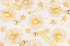 Stelle d'oro, palle e nastri sul bordo di legno bianco molle, modello, vista superiore Immagini Stock