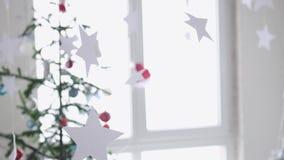 Stelle di carta che appendono per il fondo di un abete di Natale accanto alla finestra Concetto di Natale Movimento lento 4K stock footage
