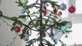 Stelle di carta che appendono per il fondo di un interno di Natale dall'abete accanto alla finestra Concetto di Natale lento video d archivio