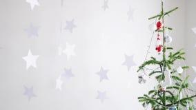 Stelle di carta che appendono per il fondo di un interno di Natale dall'abete accanto alla finestra Movimento lento Natale video d archivio