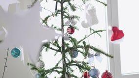 Stelle di carta che appendono su una priorità alta di un abete di Natale accanto alla finestra Concetto di Natale Movimento lento stock footage