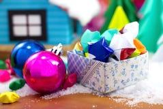 Stelle di carta in un contenitore di regalo ed in una palla di Natale sulla neve Immagini Stock