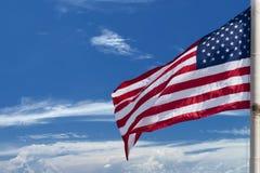 Stelle e strisce della bandiera americana degli S.U.A. sui precedenti del cielo blu Fotografia Stock Libera da Diritti