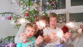 Stelle filante accese famiglia felice al partito Nei precedenti, nelle luci del bokeh e nelle ghirlande dell'abete di Natale stock footage