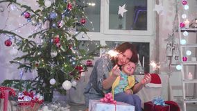 Stelle filante accese famiglia felice al partito Nei precedenti, nelle luci del bokeh e nelle ghirlande dell'abete di Natale archivi video