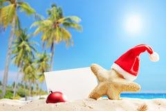 Stelle marine con il cappello di Santa ed insegna su una spiaggia Fotografie Stock