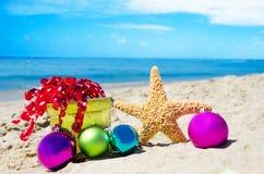 Stelle marine con le palle del contenitore e di natale di regalo sulla spiaggia Fotografie Stock