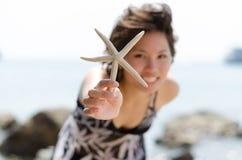 Stelle marine della stretta della donna Fotografie Stock