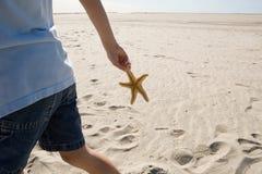 Stelle marine della tenuta del ragazzo che camminano sulla spiaggia Fotografia Stock Libera da Diritti