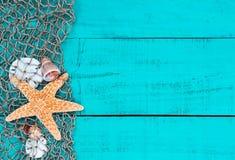 Stelle marine e coperture nel reticolato del pesce sul segno di legno blu dell'alzavola Immagini Stock