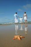 Stelle marine e famiglia tranquilla sulla spiaggia Fotografia Stock Libera da Diritti