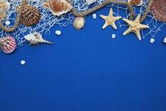 Stelle marine, Shell, pietre, corda e rete contro un fondo blu con lo spazio della copia Estate Holliday Nautico, concetto di Mar immagine stock