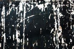 Stellen der weißen Farbe auf einer schwarzen Wand Stockfoto