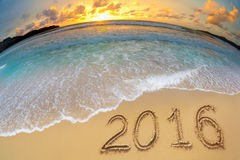 2016 Stellen des neuen Jahres geschrieben auf Strandsand Stockbild