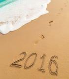 2016 Stellen des neuen Jahres geschrieben auf Strandsand Lizenzfreies Stockbild