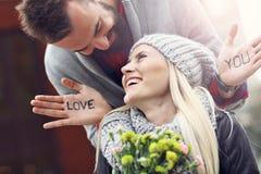 Stellen Sie das Zeigen von jungen Paaren mit den Blumen dar, die in der Stadt datieren Stockbild