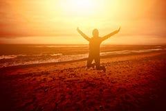 Stellen Sie die Person dar, die auf den Strand bei Sonnenuntergang springt Lizenzfreie Stockfotos