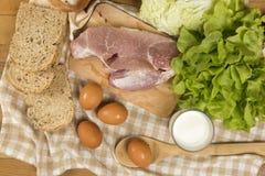 Stellen Sie die Produkte ein, die Brot, Milch, Schweinefleisch, Eiern und aus Gemüse auf Holztisch bestehen stockfoto