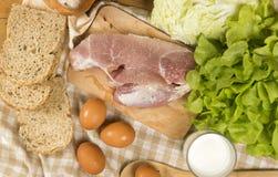 Stellen Sie die Produkte ein, die Brot, Milch, Schweinefleisch, Eiern und aus Gemüse auf Holztisch bestehen lizenzfreie stockfotos