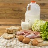 Stellen Sie die Produkte ein, die Brot, Milch, Schweinefleisch, Eiern und aus Gemüse auf Holztischhintergrund bestehen lizenzfreie stockfotos