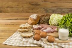 Stellen Sie die Produkte ein, die Brot, Milch, Schweinefleisch, Eiern und aus Gemüse auf Holztischhintergrund bestehen lizenzfreie stockbilder
