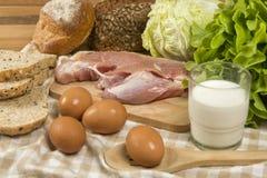 Stellen Sie die Produkte ein, die Brot, Milch, Schweinefleisch, Eiern und aus Gemüse auf Holztischhintergrund bestehen stockbild