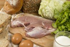 Stellen Sie die Produkte ein, die Brot, Milch, Schweinefleisch, Eiern und aus Gemüse auf Holztischhintergrund bestehen stockfoto