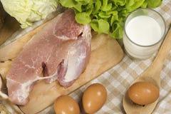 Stellen Sie die Produkte ein, die Brot, Milch, Schweinefleisch, Eiern und aus Gemüse auf Holztischhintergrund bestehen lizenzfreie stockfotografie