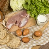 Stellen Sie die Produkte ein, die Brot, Milch, Schweinefleisch, Eiern und aus Gemüse auf Holztischhintergrund bestehen lizenzfreies stockfoto