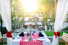 Stellen Sie die Tabelle für Abendessen mit romantischem Artblick des Weins der Sonnenuntergang ein Lizenzfreie Stockbilder