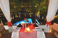 Stellen Sie die Tabelle für Abendessen mit romantischer Art des Weins nahe dem Pool für Jahrestag ein Stockfoto